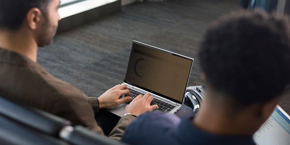 한 남자가 화면을 어둡게 만들고 프라이버시 화면으로 측면에서 읽을 수 없도록 HP 확실한보기를 켰습니다